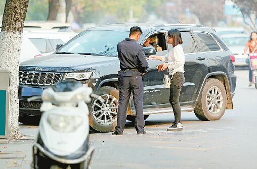 9日,趵突泉南门西侧,一名收费员在收取停车费。 记者李鹏飞 摄