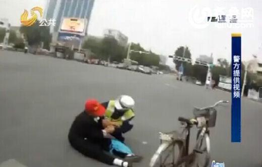 德州一位80岁的老太太骑自行车被出租车剐倒,幸亏一名女交警及时出现。(视频截图)