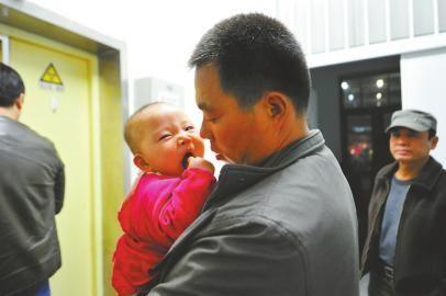 22日晚,爸爸抱着小子萱在北京儿童医院CT室外等候做检查。