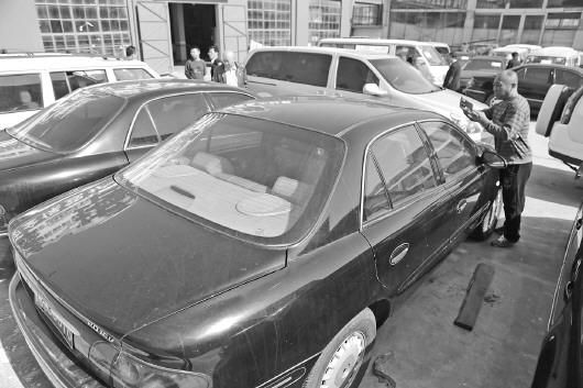 烟台市直公用旧车拍卖的消息公布后,很多市民来到汽修厂,了解这些公车的车况。 记者 韩逸 摄