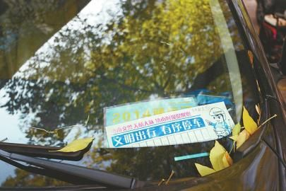 25日,经七路杆石桥附近的辅道上,一辆轿车内放置着写有电话的提示牌。 记者张刚 摄□本报记者 张晓园