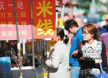 25日,市民在一小吃街上购买米线。记者张刚 摄□本报记者 张晓园
