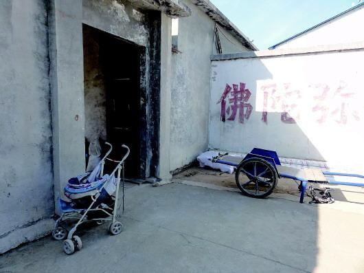 ◥停在寺院客堂门口的婴儿车。