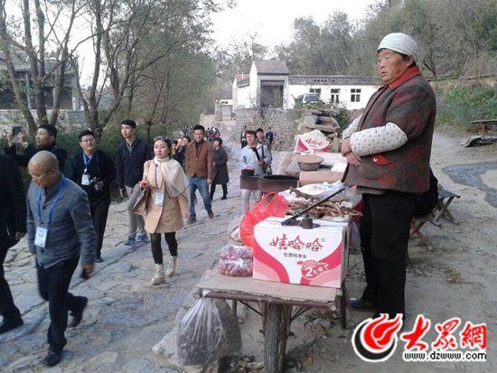 """27日,""""聚焦'一圈一带'——第十届中国网络媒体山东行""""采访团走进有着600多年历史、被称为""""齐鲁第一古村""""的章丘市朱家峪。朱家裕村民在景区内出售土特产品。"""