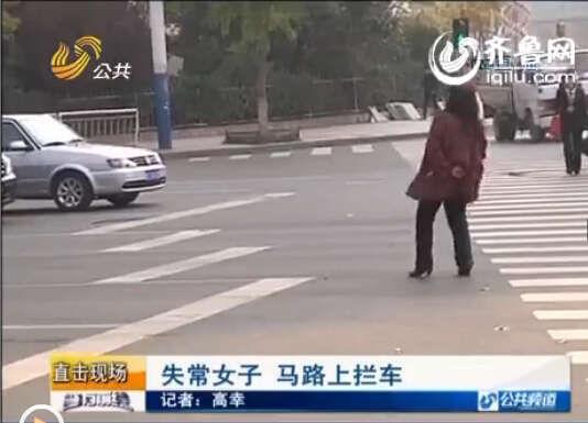 25日上午10点左右,在烟台芝罘一个十字路口,出现了一名身穿红格大衣的女子,站在马路中间跳舞,来往的车辆被她堵了一大片。