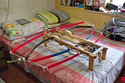 """放在床上的""""诸葛连弩""""。昨日,廖师傅展示自制的诸葛连弩。新京报记者 周岗峰 摄"""