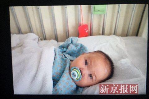 小子萱穿着浅蓝色病服,含着奶嘴儿,看见医生与护士后手舞足蹈,咯咯的笑。新京报记者 高玮 摄