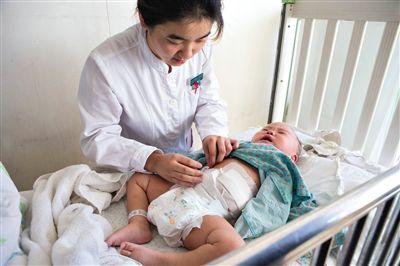 昨日,北京儿童医院,护士为即将出院的被扎钢针女婴检查伤口恢复情况。新京报记者高玮摄