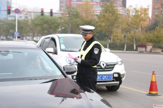 柳泉路中润大道路口交警为车主发放限行单页,对现行进行宣传。身后单号车等待出行。 记者 孙晨 摄。