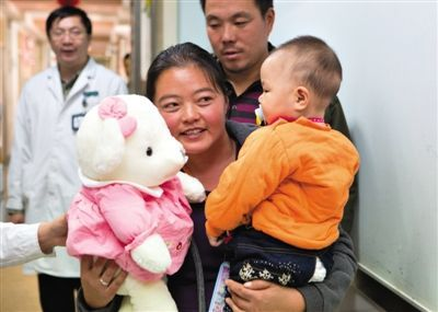 昨日上午,被扎针女婴的母亲抱着孩子和医护人员送的玩偶准备出院,院方称孩子术后恢复良好。新京报记者 高玮 摄