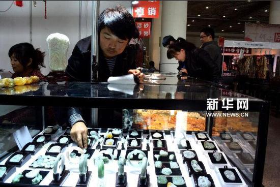 11月6日,一位参展商在山东收藏精品博览会上为顾客挑选手镯。新华社记者 冯杰摄