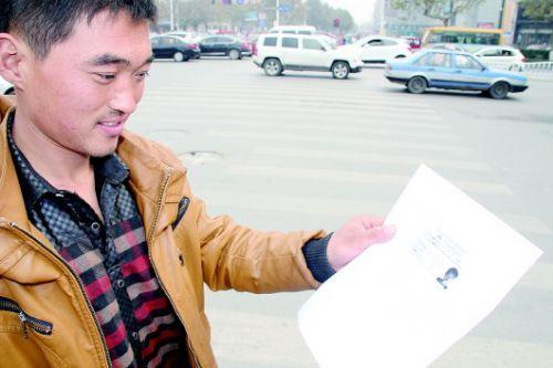 对限行不知情的车主付先生写下保证书,付先生对交警人性化执法表示感谢。齐鲁晚报记者王尚磊摄