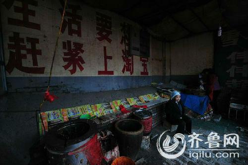 """湾头村民安大姐开了一家杀鸡摊,摊子就搭在""""生活要想好,赶紧上淘宝""""的墙体广告下。齐鲁网记者 王飞 摄"""