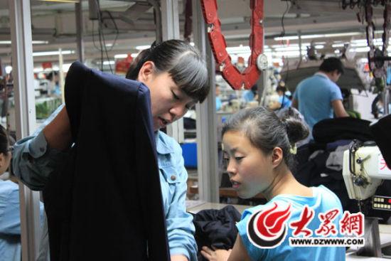 文燕(左)在生产线上对半成品进行检查。