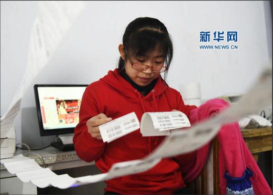 11月11日,山东省邹平县青年电商创业园内的朝阳文体商行员工在查看客户的网购订单,该商行当日的销售量比往常翻三番。新华社发(董乃德 摄)