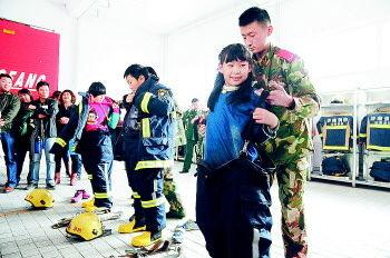 小记者试穿消防服。 记者 周青先 摄