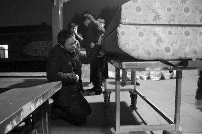 殡仪馆外,京京父亲在棺材前长跪不起,不舍得送别儿子。京华时报记者谭青摄