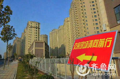 """在西蒋峪小区的主干道上,一块红色的指示牌楔写着,""""交房现场请向前行""""。齐鲁网记者 李瑞平 摄"""