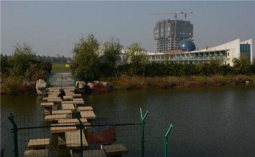"""11月6日,通往临沂大学高尔夫练习场的一条小路,铁丝网上挂着""""禁止通行""""的牌子。"""