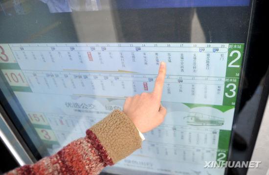 11月25日,一位济南市民正在济南市泉城路青龙桥站牌的电子屏旁观看公交车信息(朱津明摄)。