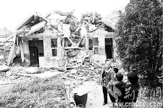 图为:孟母杨文华和家人回来看看被强拆的自家楼房
