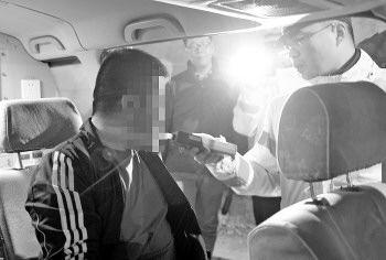 一名涉嫌酒驾的司机正在接受酒精呼吸测试。记者 吴永功 摄