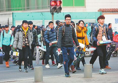 1月11日上午7点50分,在济南艺术学校考点,来自全省各地的考生们背着画板、拿着画笔和水粉颜料走进考场。(黄中明 摄)