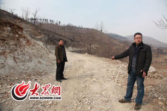 第一书记杨勇(图右)给记者从双水泉村通往官庄镇的新路