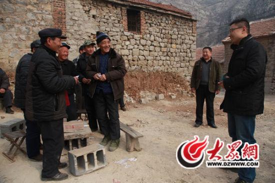 得知村民家有喜事,杨勇(右一)询问其孩子的婚礼筹备情况