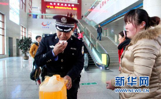 聊城站派出所副所长李传辉对旅客携带的不明液体进行认真鉴别(刘诗 摄)
