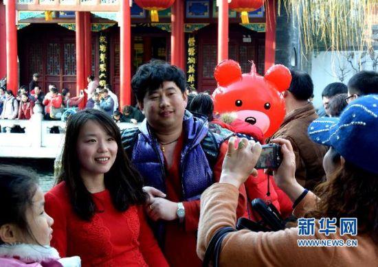 3月1日,几名游客在济南市第36届趵突泉迎春花灯会上拍照。 新华社记者 冯杰 摄