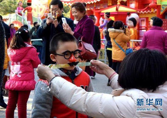3月1日,一名女士在济南市第36届趵突泉迎春花灯会上为小朋友化装。 新华社记者 冯杰 摄