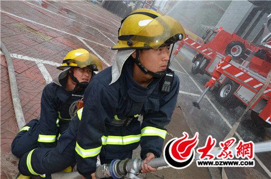 消防安全应急演练活动现场,消防员喷水救火